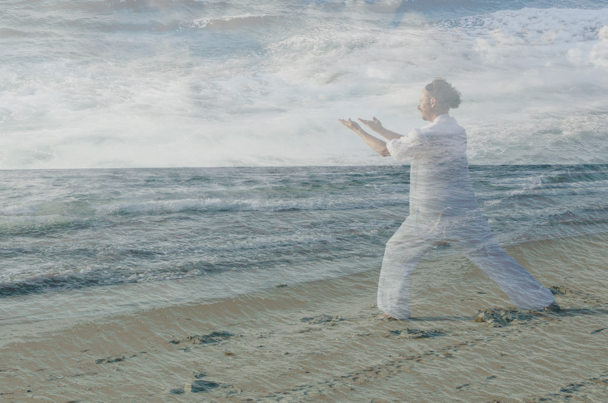 Image of man doing tai chi over part of an ocean photo